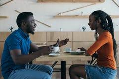 ideia lateral dos pares afro-americanos que têm a conversação durante a data imagens de stock