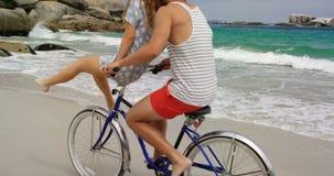 Ideia lateral dos pares caucasianos que montam uma bicicleta na praia 4k vídeos de arquivo
