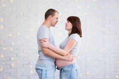 Ideia lateral dos pares grávidos felizes que abraçam sobre o wa branco do tijolo Foto de Stock