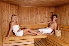Pares novos que apreciam a sauna Fotografia de Stock Royalty Free
