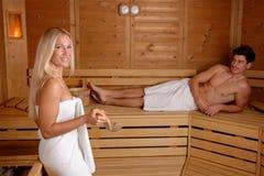 Pares novos que apreciam a sauna foto de stock
