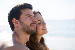Ideia lateral dos pares pensativos que sentam-se na praia Fotografia de Stock
