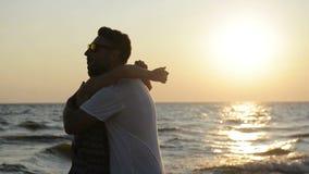 Ideia lateral dos pares Silhouetted que abraçam na praia durante o por do sol perto do mar filme