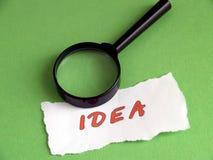 Ideia, lente de aumento no verde imagem de stock