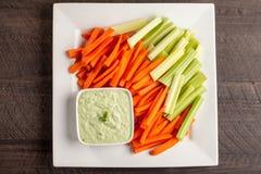 Ideia longe superior do mergulho verde com cenouras e aipo Imagens de Stock Royalty Free