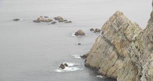 Ideia média de uma base final do penhasco com o mar que bate as rochas vídeos de arquivo