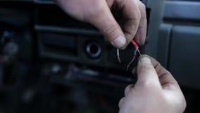Ideia macro das mãos do homem que tentam conectar e amarrar dois cabos vermelhos desencapados no carro video estoque