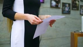 Ideia parcial das mãos da mulher que guardam uma lista ao dar uma conversa pública filme