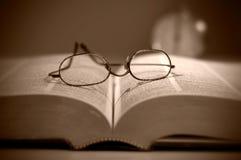 A ideia próxima de ler monóculos no grande Sepia do livro tonificou imagens de stock