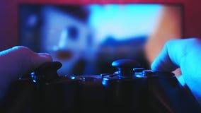 A ideia próxima de um ` s do gamer entrega o jogo do atirador em seu console do jogo usando o manche vídeos de arquivo