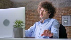 Ideia que vem à mente do programador do lerdo com cabelo encaracolado do volume, trabalhando no portátil e sentando-se no escritó filme