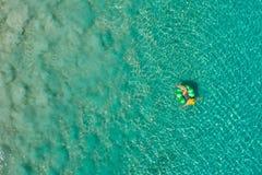 Ideia a?rea da nata??o magro da mulher na filh?s do anel da nadada no mar transparente de turquesa em Seychelles Seascape do ver? fotografia de stock