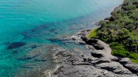 Ideia a?rea da superf?cie azul do mar na costa rochosa com reflex?es claras Ideia superior da superf?cie da ?gua do oceano de tur filme