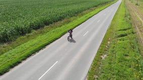 Ideia a?rea de um campo de milho verde Motociclista com uma criança que monta uma motocicleta em uma estrada asfaltada ao longo d vídeos de arquivo