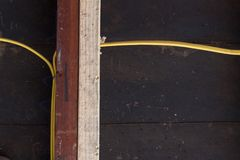 Ideia reta de sistering de parafusos prisioneiros velhos e novos da parede para o apoio estrutural, fiação elétrica amarela contr foto de stock