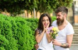 Ideia sempre boa do ramalhete Traga-lhe flores favoritas Surpresa para ela O homem dá a menina do ramalhete da flor a data românt imagem de stock royalty free