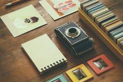 Ideia superior da câmera do vintage e de quadros velhos das corrediças sobre o fundo de madeira da tabela Fotografia de Stock