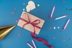 Ideia superior da caixa de presente, do chapéu do aniversário e das velas no azul Foto de Stock Royalty Free
