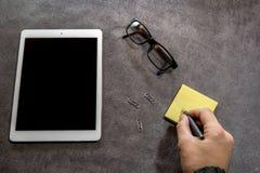 Ideia superior da escrita da mão do homem no papel na mesa Foto de Stock Royalty Free