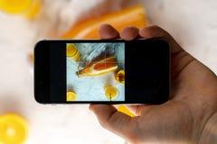Ideia superior da mão que guarda um telefone que faz uma fotografia do alimento dos móbeis imagens de stock