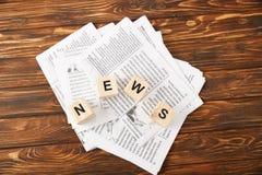 ideia superior da notícia da palavra feita de cubos do alfabeto no montão dos jornais no fundo de madeira foto de stock royalty free