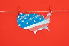 Ideia superior da parte de mapa com a bandeira americana que pendura na corda isolada no vermelho Fotografia de Stock Royalty Free