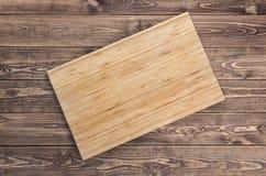 Ideia superior da placa de corte de madeira na tabela de madeira velha Foto de Stock