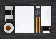 Ideia superior da zombaria dos artigos de papelaria da identidade de marcagem com ferro quente acima na tabela preta Foto de Stock