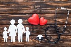 ideia superior das figuras brancas da família que guardam as mãos, símbolos vermelhos dos corações e estetoscópio em de madeira imagens de stock