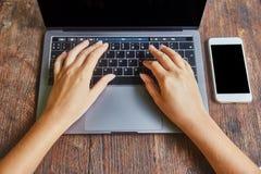 Ideia superior das mãos bonitas da mulher que datilografam no teclado numérico do portátil colocado no desktop de madeira do escr fotos de stock royalty free
