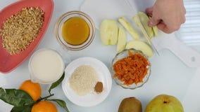 Ideia superior das mãos da mulher que cortam a maçã na placa de desbastamento em uma cozinha Cozinhando o alimento saudável 4 K video estoque