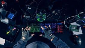 Ideia superior das mãos do hacker masculino que datilografam em um teclado iluminado vídeos de arquivo