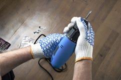 Ideia superior das mãos masculinas usando o skrewdriver elétrico contra o assoalho de madeira Processo de reparo fotos de stock royalty free