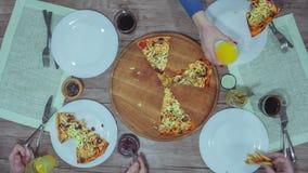 A ideia superior das mãos que tomam a pizza corta da placa na tabela vídeos de arquivo
