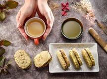 Ideia superior das mãos que vão tomar a pronunciação do francês do dacquoise do chá verde e do matcha fotos de stock royalty free