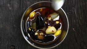 Ideia superior de comer a sobremesa misturada deliciosa fria do feijão e do cereal no xarope vídeos de arquivo