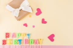 Ideia superior de corações da rotulação, da caixa de presente e do papel do feliz aniversario no bege Imagens de Stock Royalty Free