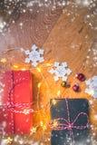 Ideia superior de decorações dos presentes, do floco de neve do Natal, de bolas do Natal e de luzes no fundo de madeira com folha foto de stock royalty free