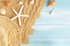 Ideia superior de escudos do chapéu e do mar de palha do mar na areia do mar em um fundo de madeira azul, conceito do verão no as foto de stock royalty free