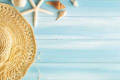 Ideia superior de escudos do chapéu e do mar de palha do mar no fundo de madeira azul, no conceito do verão no assoalho de madeir imagens de stock