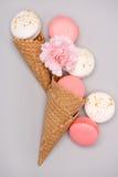 Ideia superior de macarons cor-de-rosa e brancos em cones do waffle com flor do cravo Imagens de Stock