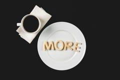 Ideia superior de mais palavra feita da massa da cookie na placa com copo de café Fotos de Stock