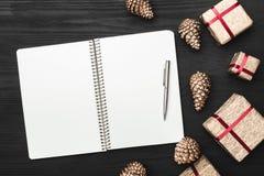 Ideia superior, superior, de presentes de Natal em um fundo rústico preto de madeira, almofada de nota fotografia de stock royalty free