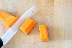 A ideia superior de um corte cerâmico da faca cuba uma abóbora Imagem de Stock