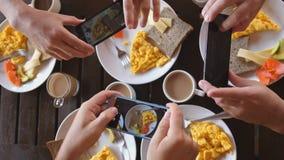 Ideia superior de um grupo de amigos que comem o café da manhã em um café na tabela de madeira, tomando a imagem da omeleta, os b fotografia de stock