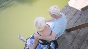 Ideia superior de um par maduro feliz que senta-se no banco perto do rio, admirando a natureza Mulher superior que beija seu mari video estoque