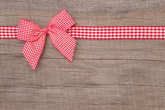 A ideia superior de um vermelho verificou a decoração da fita no fundo de madeira fotografia de stock royalty free