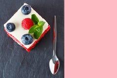 Ideia superior de uma fatia de bolo decorada com mirtilos e framboesas no fundo cor-de-rosa Bolo vermelho de veludo com bagas Imagem de Stock