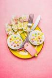 Ideia superior do ajuste de lugar festivo da tabela com bolo, flores do narciso, cutelaria e a etiqueta vazia no fundo do rosa pa Fotos de Stock