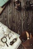 ideia superior do arranjo com mapa, lupa, saco, compasso e a câmera retro da foto na obscuridade foto de stock